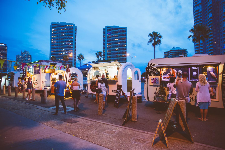 Evening street food caravans with people wandering around.