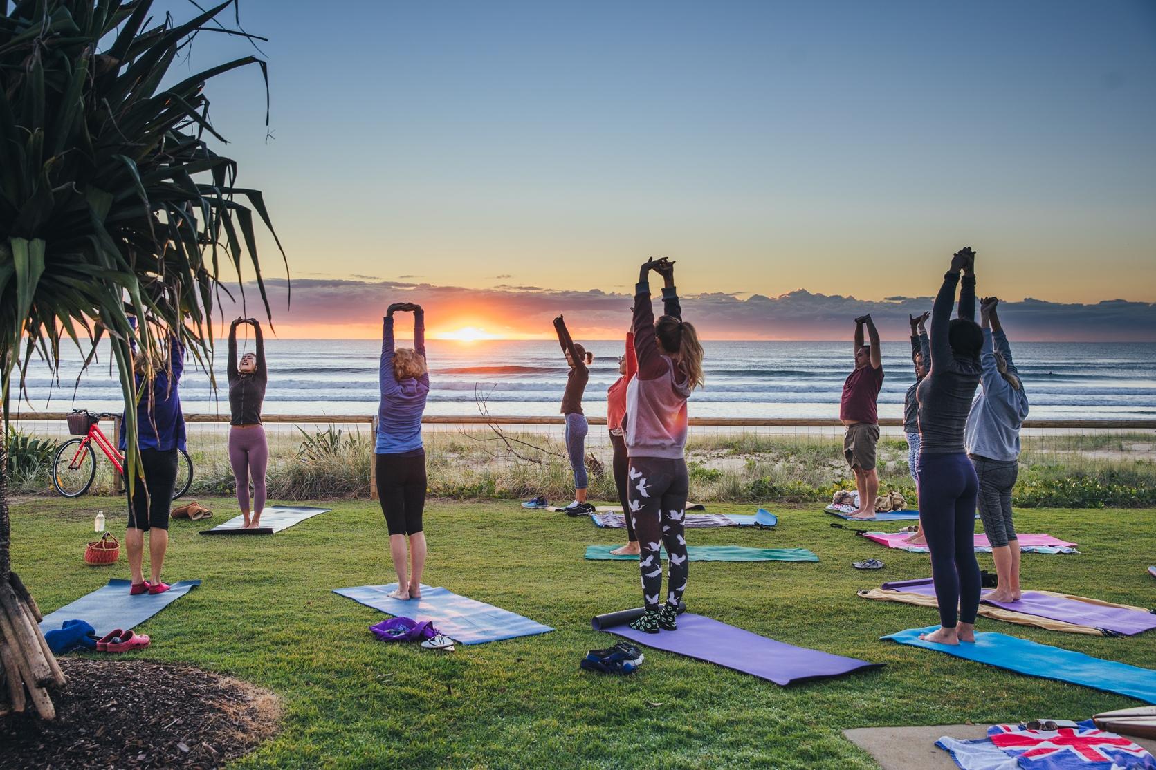 Yoga at sunrise by a beach
