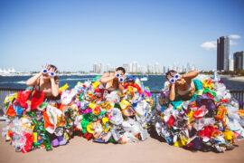 three people standing outdoors wearing dresses made out of plastic waste