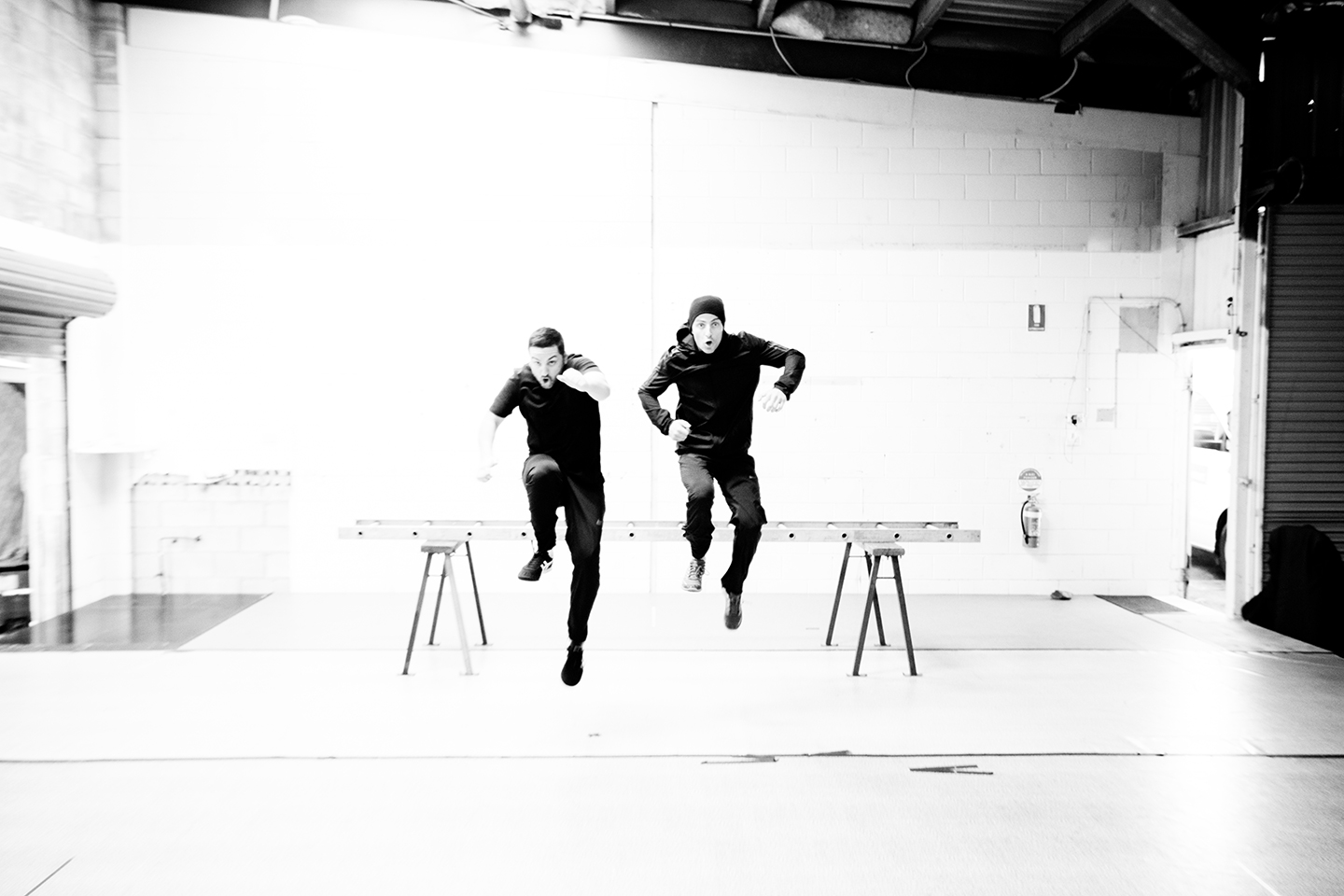 black and white photo of two people in a warehouse jumping at the same time
