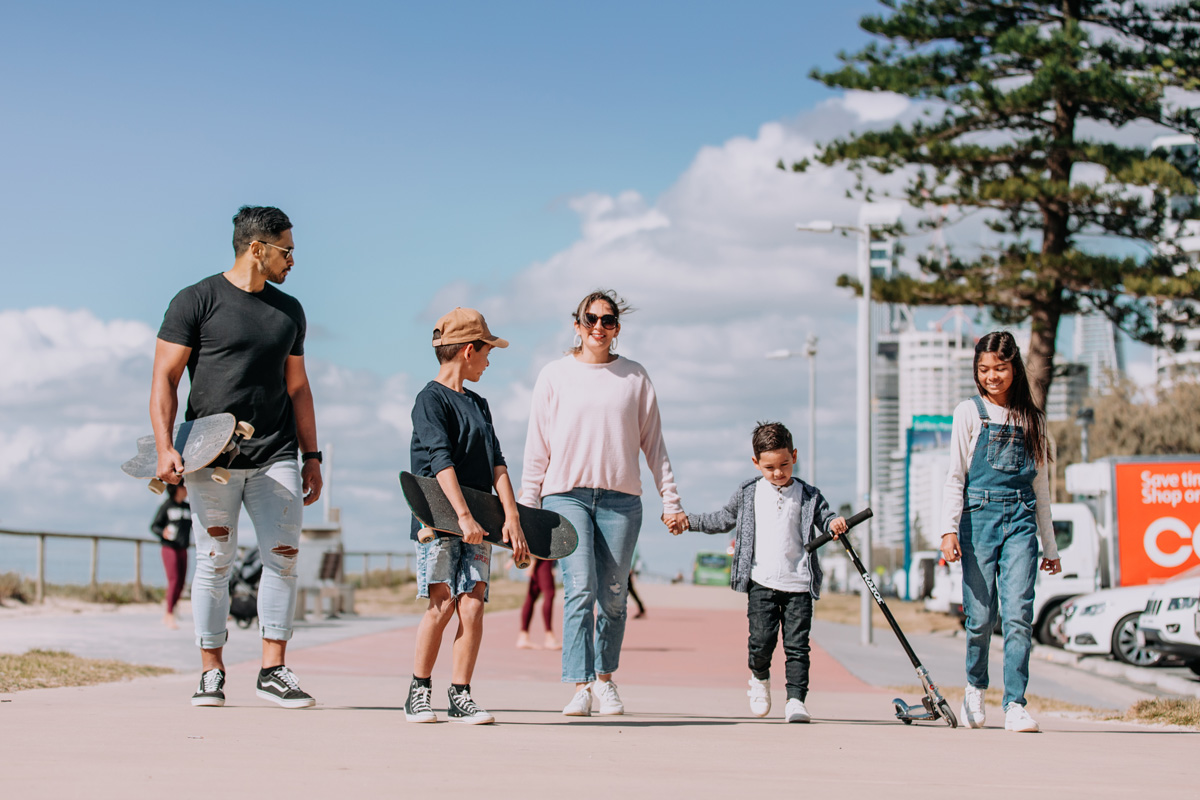 five family members walking on a pathway by the beach holding skateboards and scooters