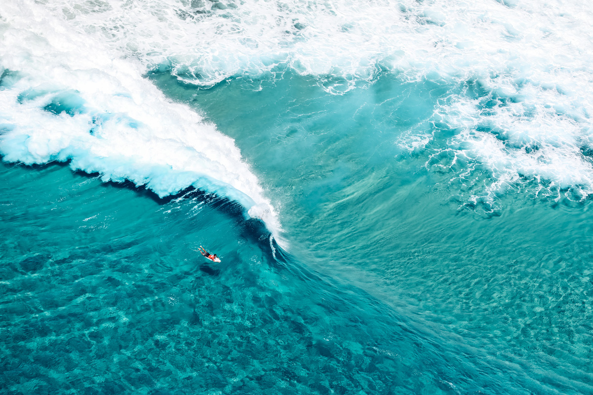 a top down shot of a person surfing on clear blue water