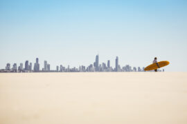 one surfer standing by the beach with the Gold Coast skyline in the backgorund