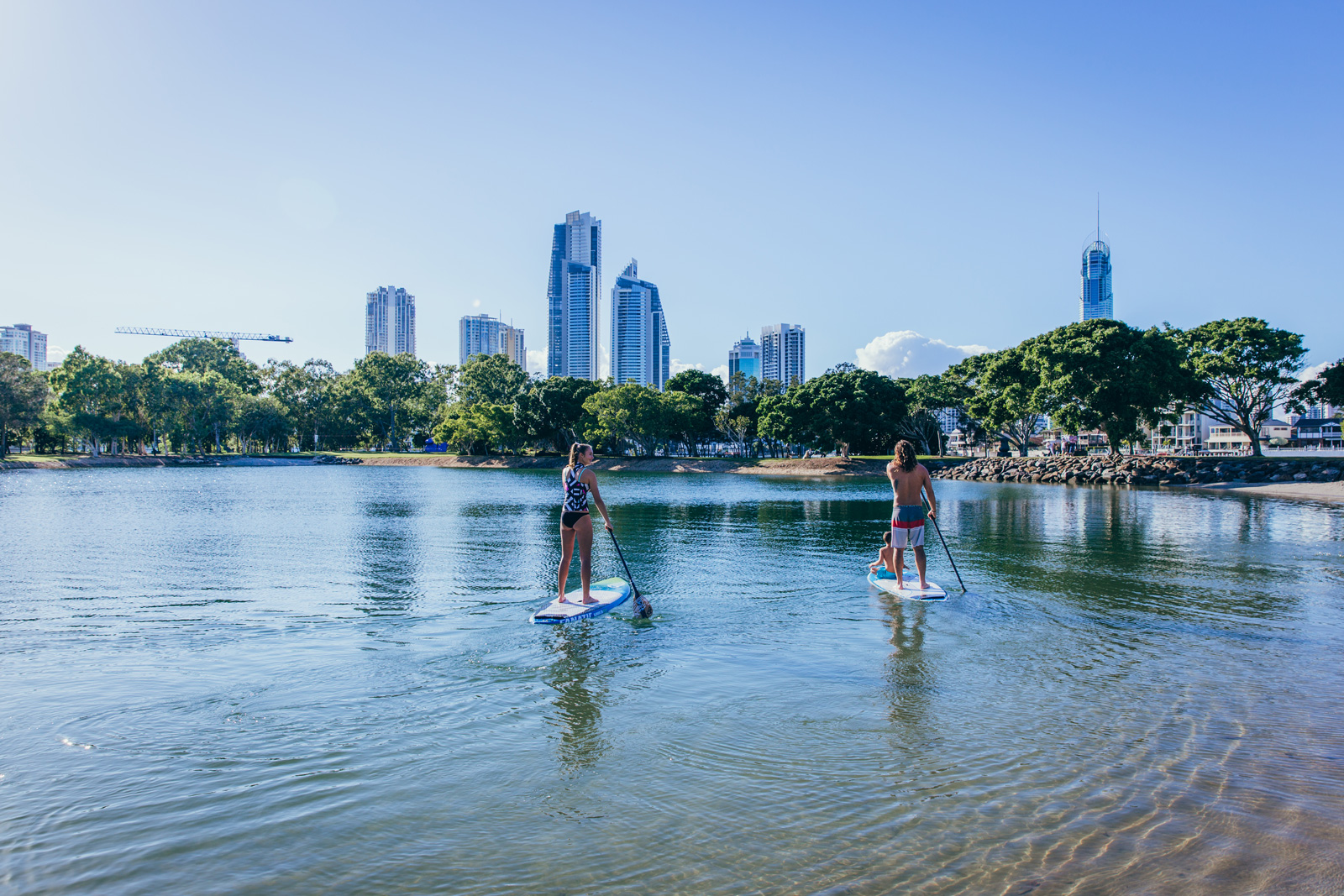 two people paddle-boarding on the water with the Gold Coast skyline in the background