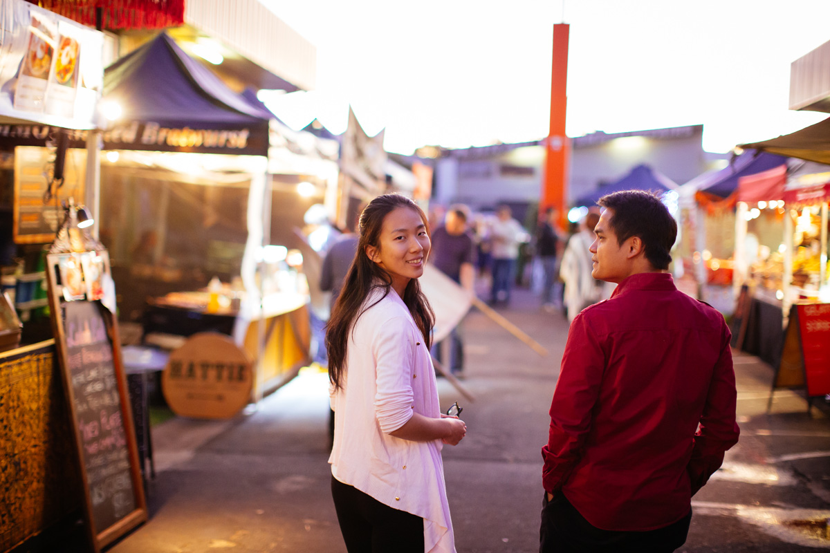 two people walking on a street with markets on either side, with one person turning around to face the camera